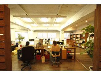 机やソファなど木目のインテリアに囲まれデザインと編集が協力して制作しています
